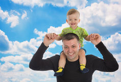 Little son sits on father shoulders. Outdoors Stock Photo