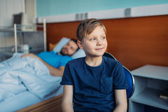 Little son sitting on chair near his sick father sleeping on hospital bed at ward Royalty Free Stock Image