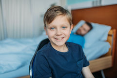 Little son sitting on chair near his sick father sleeping on hospital bed at ward Royalty Free Stock Photos