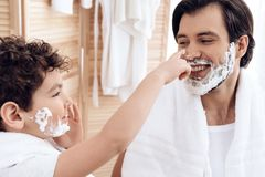 Little son spoils father`s nose with shaving foam. stock images
