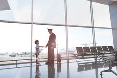 Little son standing near pilot. Small boy is seeing off his father aviator nearby tremendous window. They looking at each other. Copy space on right side Royalty Free Stock Image