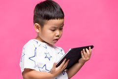 Little son watching on digital tablet. Asian young little boy stock photo