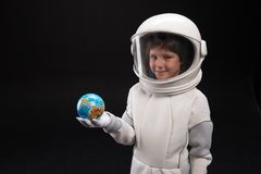 Little spaceman is expressing gladness. My motherland. Waist up portrait of optimistic boy astronaut wearing helmet is standing and holding small globe of earth royalty free stock image