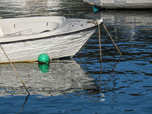 Little Sparrow- Lyme Regis Harbour. Small skiff with reflections at Lyme Regis harbour on a calm autumn morning stock photos