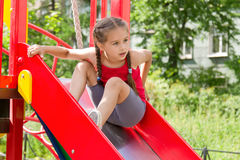 Little sportive girl playing on playground, sitting on the slide Stock Photography