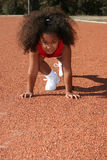 Little sports girl. Front view of a cute little multiracial girl with black long curly hair on the marks on a sports field Royalty Free Stock Photos