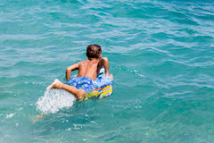 Little sporty boy with a surfboard royalty free stock photography
