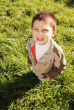 Little squinting boy. In casual clothes looking up Stock Photography
