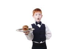 Little ssuprised waiter serves hamburger isolated on white Stock Images