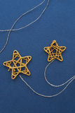 Little stars. Little Christmas golden stars on blue fabric background Royalty Free Stock Photo