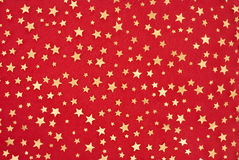 Little stars. Little golden stars on red background Stock Images