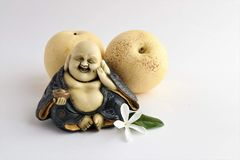 Little statue of laughing Buddha with pears royalty free stock images