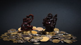 Little status on a pile of money. Little statues sitting on a big pile of coins bringing good luck Stock Photos