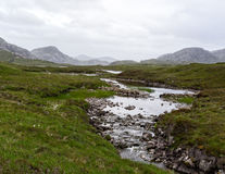 A little stream through the Scottish highlands. River flowing through the peat landscape in Scotland Royalty Free Stock Images