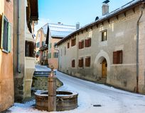 Little street with typical houses and fountain in the older part of Guarda, Inn District, Swiss canton of Graubunden, Switzerlan. D stock photography