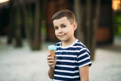 A little in a stripper t-shirt is eating blue ice cream. Spring sunny weather Stock Photography