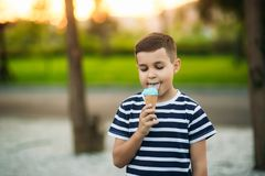A little in a stripper t-shirt is eating blue ice cream. Spring sunny weather Royalty Free Stock Images