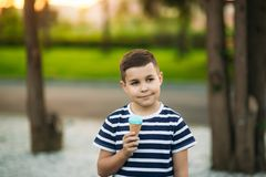 A little in a stripper t-shirt is eating blue ice cream. Spring sunny weather Royalty Free Stock Photography