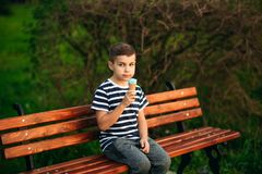A little in a stripper t-shirt is eating blue ice cream. Spring sunny weather Stock Photo