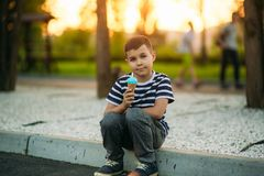 A little in a stripper t-shirt is eating blue ice cream. Spring sunny weather Stock Photos
