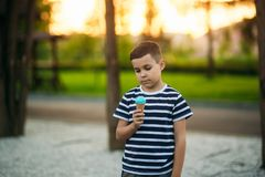 A little in a stripper t-shirt is eating blue ice cream. Spring sunny weather Royalty Free Stock Photos