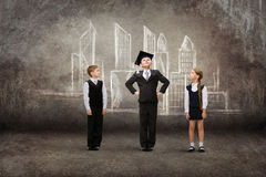 Little student in academic cap with friends against city drawing Royalty Free Stock Image