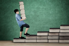 Little student carrying books on staircase Royalty Free Stock Image