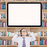 Little student find idea in library. Thoughtful little schoolboy looks thinking an idea under empty whiteboard in the library Royalty Free Stock Images