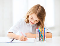Little student girl drawing at school Royalty Free Stock Photos