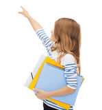 Little student girl with notebooks pointing to Stock Photo