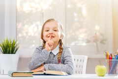 Free Little Student Girl Sitting At The Table And Reading A Book. The Child Shows A Sign Shh. The Concept Of Education And School. Royalty Free Stock Photo - 157885795