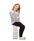 Little student girl sitting on stack of books Royalty Free Stock Image