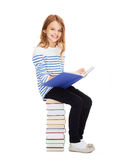Little student girl sitting on stack of books Stock Images