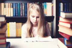 Little student girl studying and reading book at school Stock Photography