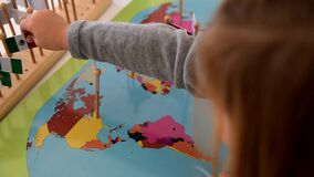 Little student girl trying match flags with countries on a Montessori map