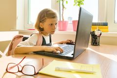 Little student girl of 8 years old in school uniform with a backpack uses computer laptop. School, education, knowledge and. Children stock photos