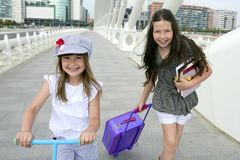Little student girls going to school in city Royalty Free Stock Photos