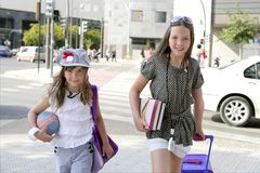 Little student girls going to school in city. Little girls going to school with bags, books and student stuff Stock Photos