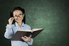 Little student holding textbook. While wearing glasses with copy space on the chalkboard Stock Images