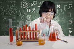 Little student makes chemical experiments. Photo of a little student makes chemical experiments in the lab with doodles on the blackboard Royalty Free Stock Photo