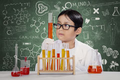 Little student makes chemistry experiment. Portrait of male student wearing coat and make chemistry experiment in the lab with scribble background on the Stock Photos