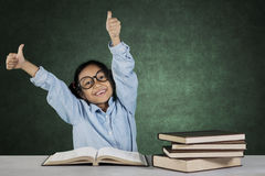 Little student showing ok gesture with books Stock Images