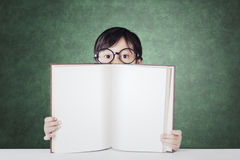 Little student shows empty book in the classroom. Little schoolgirl wearing glasses in the class and showing empty book with chalkboard background Royalty Free Stock Images