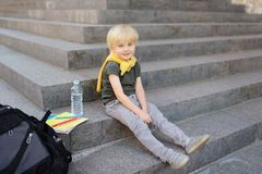 Little student sitting on staircase near the school building. Back to school stock photos