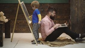 Little student with smiling teacher in classroom. Side view adorable little kid writing on chalkboard. Cool guy in pink. Shirt sitting on floor with laptop next stock video footage