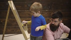 Little student with smiling teacher in classroom. Side view adorable kid writing on chalkboard. Early learning concept. Wooden background. Bearded man in stock footage