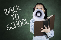 Little student speaking on megaphone in classroom Royalty Free Stock Photography