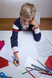 Little student writing in notebook Stock Image