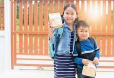 Little students holding lunch bag before go to school stock image