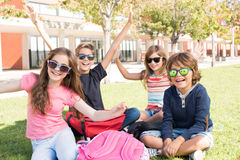 Little students at School Campus. Group of little students sitting on the grass at school royalty free stock photos